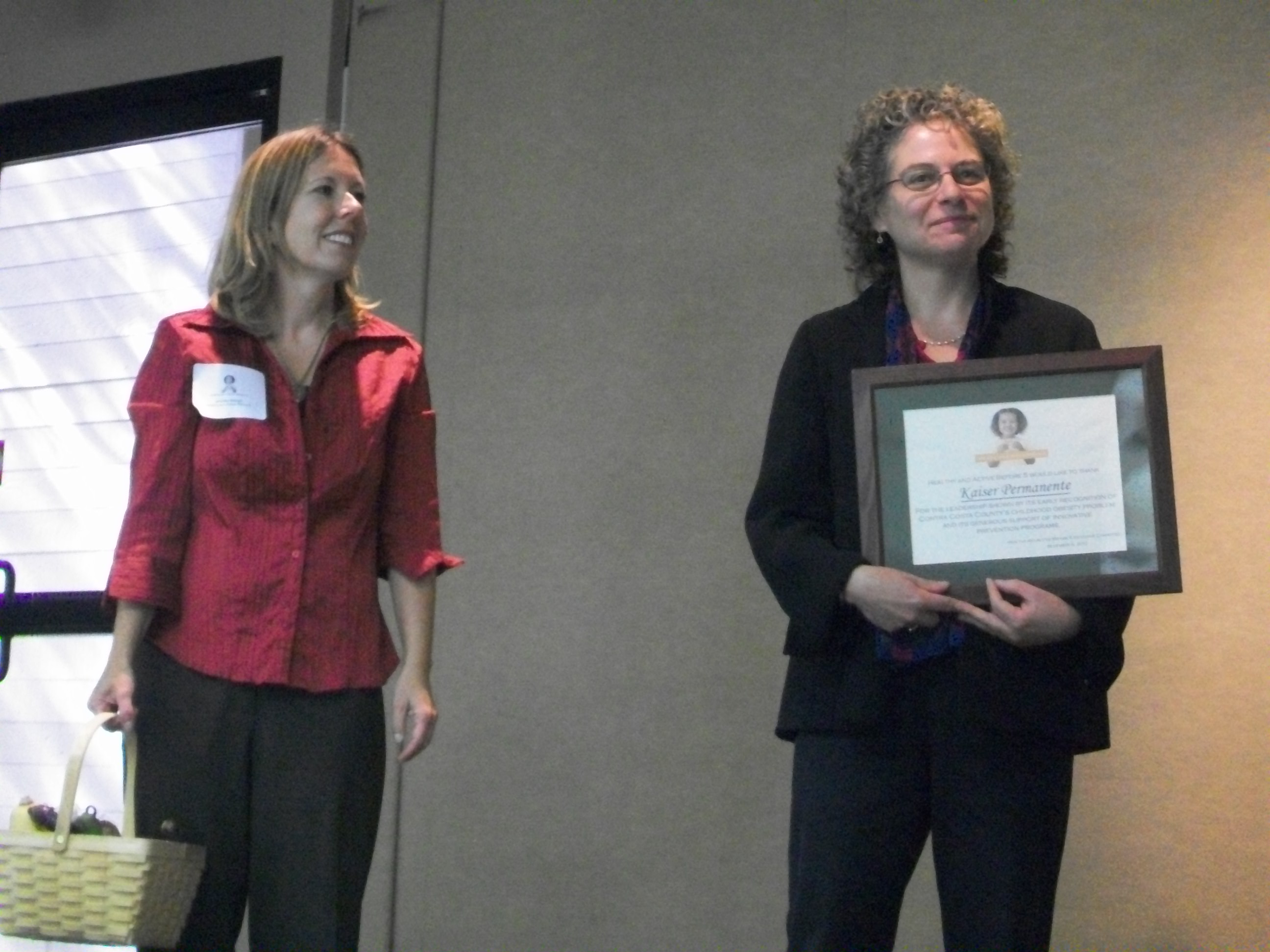 Program Manager Jean Nudelman stands next to Jean Nudelman who accepts the award on behalf of Kaiser Permanente
